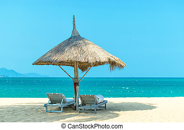 Idyllic landscape paradise scene at the beach with strawy loungers on clear blue sky day