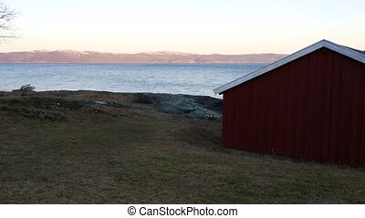 idyllic located red wooden house at scandinavian fjord