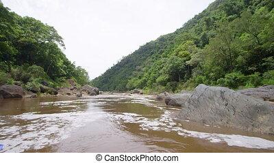 Idyllic muddy stream - Shot in slow motion, the stream looks...