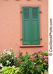 idyllic old house with folding shutters and plants