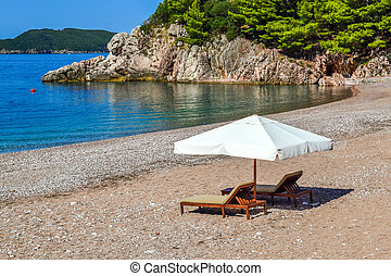 Idyllic scene of deck chairs under an umbrella on a clean beach in the hot afternoon sun.