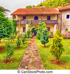 stone rural house with pretty cottage garden