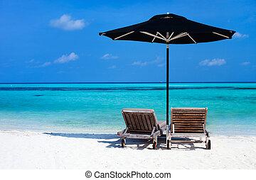 Idyllic tropical beach at Maldives - Chairs and black ...