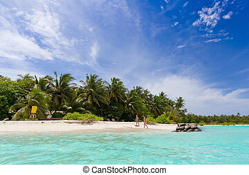 Children walking on idyllic beach with blue sky and cloudscape background, Maldives.
