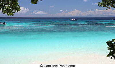 Idyllic tropical turquoise beach with white sand shore and boat at andaman sea Koh Tachai Island Thailand