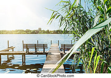 idyllic view of Havel river in Berlin with pier and reeds on riverbank under blue summer sky