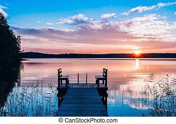 Idyllic view of the long pier with wooden bench on the lake. Sunset or sunrise over the water.
