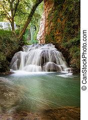 Idyllic Waterfall in rainforest landscape. Water flowing in tranquil scenery.