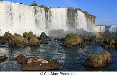 Igaucu falls with rainbow and rocks - Iguassu Falls is the...