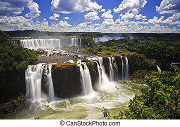 Iguassu Falls is the largest series of waterfalls on the planet, located in Brazil, Argentina, and Paraguay. At some times during the year one can see as many as 275 separate waterfalls cascading along the edges of 2,700 meters (1.6 miles) cliffs. Argentines spells this wonder, �Iguazu�, the ...