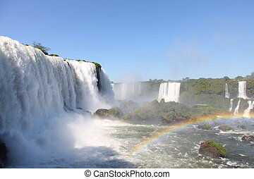 Iguassu waterfalls with rainbow on a sunny day early in the ...