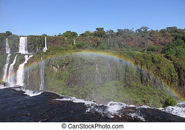 Iguassu waterfalls with rainbow on a sunny day early in the morning. The biggest waterfalls on earth.