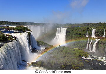 Iguazu waterfalls with rainbow on a sunny day. The largest waterfall on earth