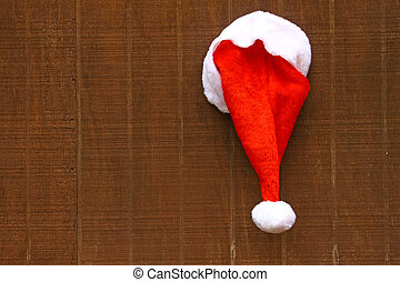 Iimage of Santa's hat hanging on a wooden backdrop with copy space.