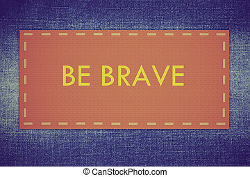 Be brave: Inspirational motivating quote on jeans fabric background.