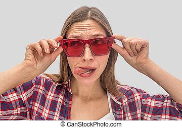 il, isolé, par, regarde, fin, rigolote, stands, tient, jeune, arrière-plan., role., rouges, spectacles, femme, sunglasses., mains, tongue., deux, gris, elle, jouer, gauche