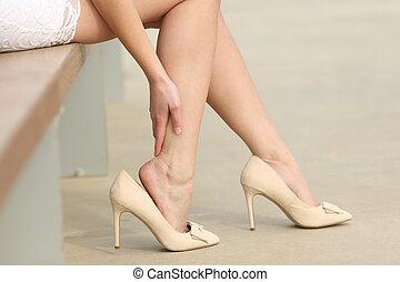 il portare, donna, alto, toccante, talloni, gambe, doloroso