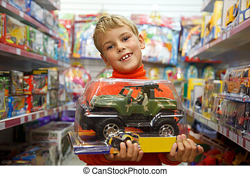 il, ragazzo, in, negozio, con, il, giocattolo, macchina, in, mani