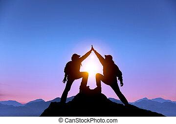il, silhouette, di, due, uomo, con, successo, gesto, standing, su, il, cima, di, montagna
