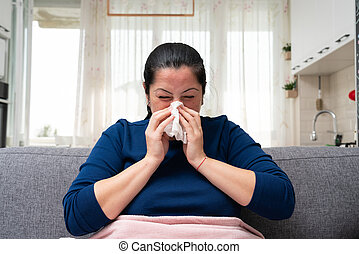 Ill adult woman blowing nose feeling unwell with cold symptoms