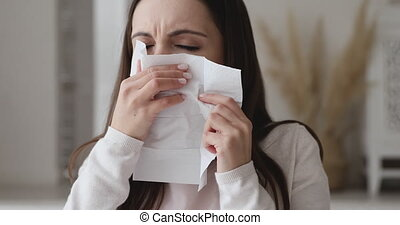 Ill allergic young woman sneezing in tissue blowing running nose. Sick girl got flu concept or caught cold, having allergy symptoms. Unhealthy lady suffer from seasonal virus disease. Close up view