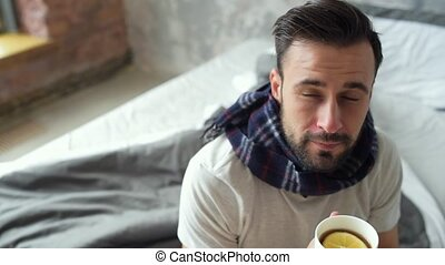Ill gentleman fixing scarf while drinking tea - Recovering...