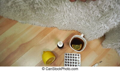 ill girl lies under a blanket on the couch with medications on the floor