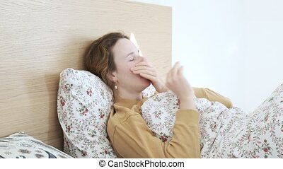 ill girl sneezing, blowing, wiping nose with tissue paper. woman coughs in bed