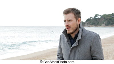 Ill man coughing in a cold day on the beach - Ill man...