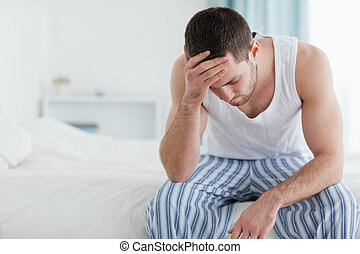 Ill man sitting on his bed with his head on his hand