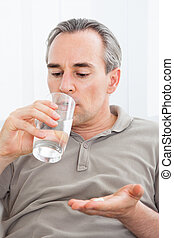 Ill man taking medication sitting up holding a glass of...