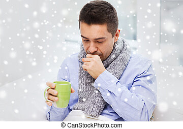 ill man with flu drinking tea and coughing at home