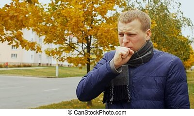 ill or sick man coughs in the city or outdoor due to...