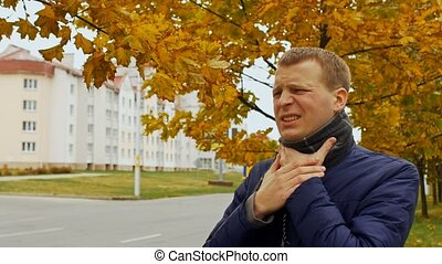 ill or sick man has sore throat in city or outdoor in autumn...