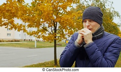 ill or sick man shivers due to cold autumn or fall weather...