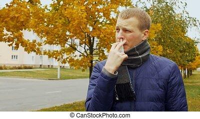 ill or sick man uses medicinal nasal spray against stuffy...