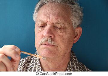 ill senior checks his fever - older man frowns as he looks...
