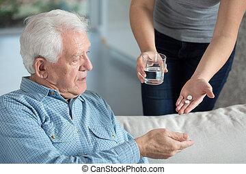 Ill senior man taking medicine - Close-up of ill senior man...