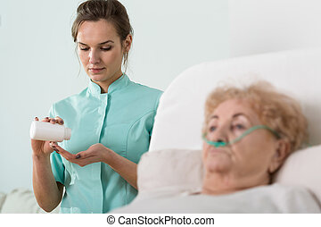 Ill senior woman and nurse