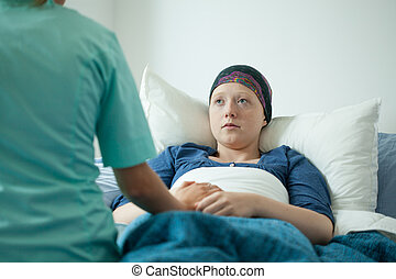 Ill with cancer girl talking with doctor