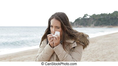 Ill woman coughing in a cold day on the beach - Ill woman...