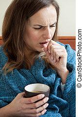 Ill woman drinking tea - Ill woman in bed drinking tea,...