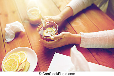 ill woman drinking tea with lemon and ginger