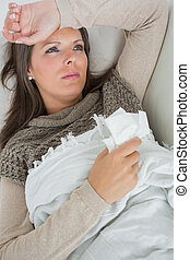 Ill woman lying on sofa
