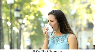 Ill woman sneezing in the street - Ill woman sneezing...