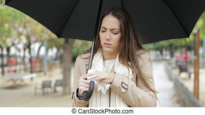 Ill woman sneezing walking under the rain - Front view of an...