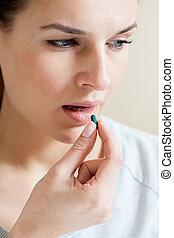Ill woman taking a pill