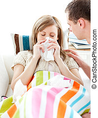 Ill woman with tissue lying on a sofa with her boyfriend