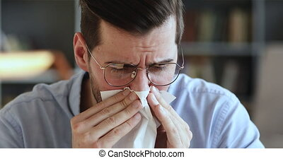 Ill young man having allergy symptoms blowing running stuffy nose in tissue. Unhealthy businessman suffering from sniffles, allergic rhinitis concept sitting at home or in office. Close up view