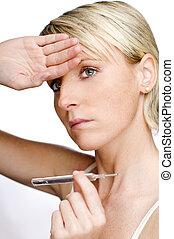 ill - young woman checking temperature close up shoot